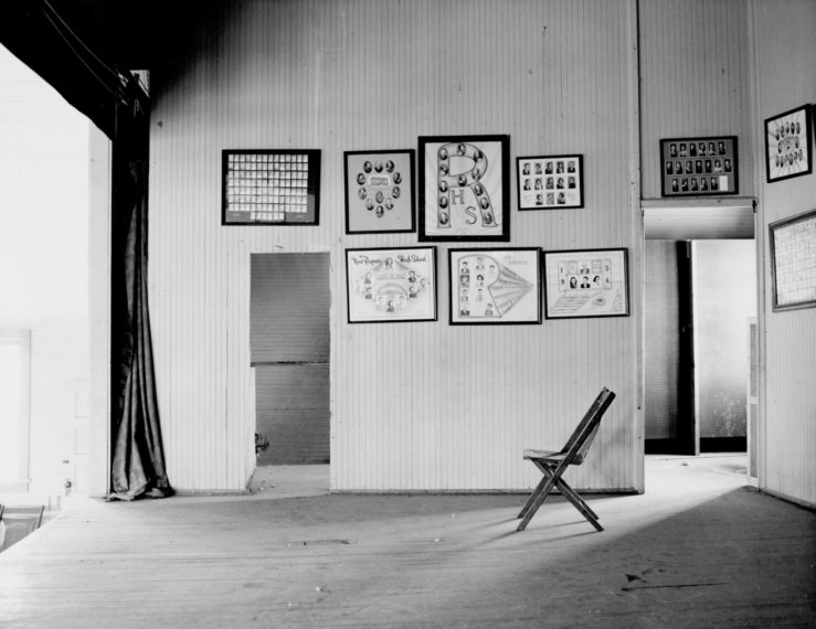 Pictures of graduating classes, on a stage at the end of a gymnasium in a consolidated school (closed), New Raymer, Weld County, Colorado, 1970, gelatin-silver print