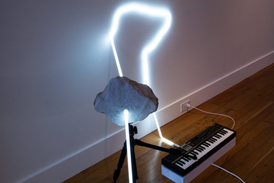 Richard T. Walker, in defiance of being here #9, 2016, neon, tripod, rock, and Casiotone MT 68 keyboard